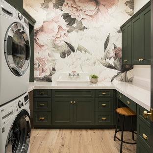 Esempio di una sala lavanderia classica con top in quarzo composito, ante in stile shaker, ante verdi, parquet chiaro, lavatrice e asciugatrice a colonna, pavimento marrone, top bianco e pareti multicolore