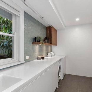 Неиссякаемый источник вдохновения для домашнего уюта: прачечная в современном стиле с одинарной раковиной, со стиральной машиной с сушилкой, коричневым полом и белой столешницей