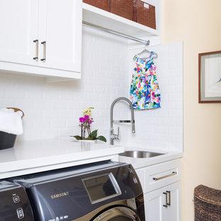 Foto på en mellanstor funkis vita linjär tvättstuga enbart för tvätt, med en undermonterad diskho, skåp i shakerstil, vita skåp, bänkskiva i kvarts, orange väggar och en tvättmaskin och torktumlare bredvid varandra