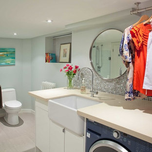 Photo of a large contemporary single-wall utility room in Toronto with a belfast sink, flat-panel cabinets, white cabinets, blue walls, a side by side washer and dryer and beige floors.