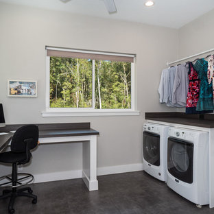 Medium sized classic single-wall utility room in Miami with a built-in sink, shaker cabinets, white cabinets, composite countertops, white walls, dark hardwood flooring, a side by side washer and dryer, brown floors and black worktops.