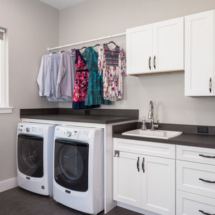 This is an example of a medium sized traditional single-wall utility room in Miami with a built-in sink, shaker cabinets, white cabinets, composite countertops, white walls, dark hardwood flooring, a side by side washer and dryer, brown floors and black worktops.