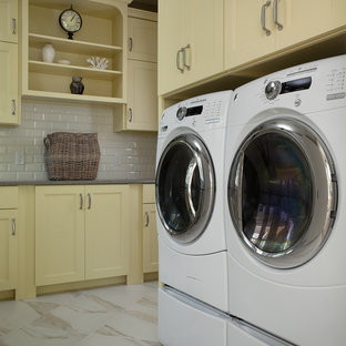 Photo of a large traditional single-wall utility room in Grand Rapids with recessed-panel cabinets, yellow cabinets, porcelain floors and a side-by-side washer and dryer.