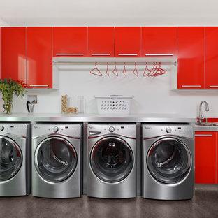 На фото: универсальная комната в современном стиле с хозяйственной раковиной, красными фасадами, белыми стенами, бетонным полом, со стиральной и сушильной машиной рядом и серым полом с