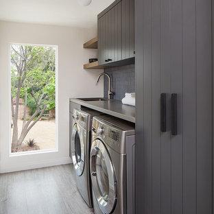Idée de décoration pour une petite buanderie minimaliste dédiée avec des portes de placard grises, un plan de travail en quartz modifié, un mur blanc, un sol en bois clair, des machines côte à côte, un sol gris, un plan de travail gris et un évier encastré.