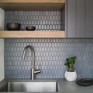 Idée de décoration pour une petite buanderie parallèle minimaliste dédiée avec un évier posé, des portes de placard grises, un plan de travail en quartz modifié, un mur blanc, un sol en bois clair, des machines côte à côte, un sol gris et un plan de travail gris.