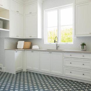 Immagine di una lavanderia multiuso mediterranea con lavello sottopiano, ante in stile shaker, ante bianche, top in quarzo composito, pareti bianche, pavimento con piastrelle in ceramica, lavatrice e asciugatrice affiancate, pavimento grigio e top grigio