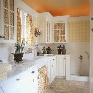 Exempel på ett klassiskt grovkök, med en rustik diskho, luckor med glaspanel, vita skåp, kaklad bänkskiva, gula väggar och en tvättmaskin och torktumlare bredvid varandra