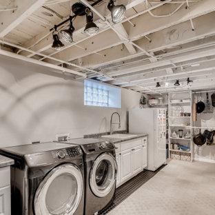 На фото: п-образная универсальная комната среднего размера с хозяйственной раковиной, столешницей из ламината, белыми стенами, ковровым покрытием, со стиральной и сушильной машиной рядом, серым полом и балками на потолке с