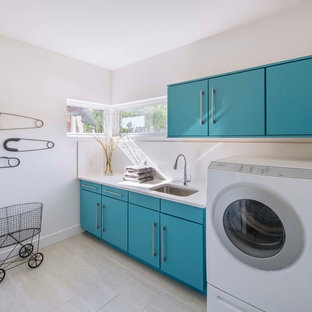 Dedicated laundry room - contemporary single-wall light wood floor dedicated laundry room idea in Austin with an undermount sink, flat-panel cabinets, blue cabinets, white walls and white countertops