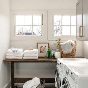 Inredning av en klassisk mellanstor linjär tvättstuga enbart för tvätt, med grå skåp, vita väggar, en tvättmaskin och torktumlare bredvid varandra, skåp i shakerstil och grönt golv