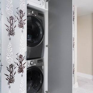 Ispirazione per un ripostiglio-lavanderia bohémian di medie dimensioni con ante lisce, ante grigie, pareti grigie, pavimento in marmo, lavatrice e asciugatrice nascoste e pavimento bianco