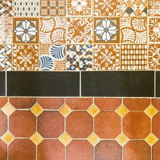 Bild på en mellanstor vintage tvättstuga, med klinkergolv i terrakotta