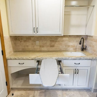 Photo of a mid-sized country utility room in Orange County with an undermount sink, white cabinets, granite benchtops, yellow walls, travertine floors, beige floor and recessed-panel cabinets.