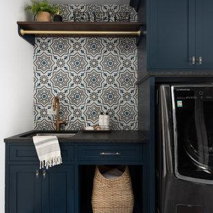 Idées déco pour une buanderie campagne avec un évier encastré, un placard à porte shaker, des portes de placard bleues, une crédence multicolore, un mur blanc, un sol gris et un plan de travail noir.