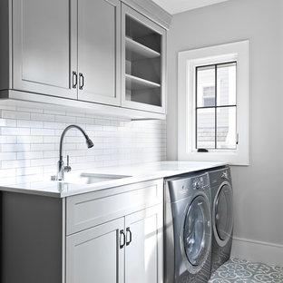 На фото: отдельные, линейные прачечные в стиле кантри с врезной раковиной, фасадами с утопленной филенкой, серыми фасадами, серыми стенами, со стиральной и сушильной машиной рядом, серым полом и белой столешницей