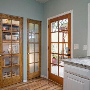 Foto di una lavanderia multiuso stile americano di medie dimensioni con lavello da incasso, ante bianche, pareti verdi, pavimento in gres porcellanato e lavatrice e asciugatrice affiancate
