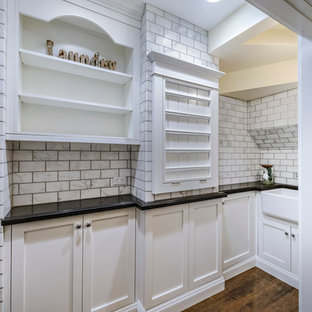 Design ideas for a medium sized traditional u-shaped utility room in San Diego with a belfast sink, shaker cabinets, white cabinets, beige walls, medium hardwood flooring, a stacked washer and dryer, brown floors and black worktops.