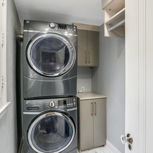 Dedicated laundry room - small transitional single-wall marble floor and white floor dedicated laundry room idea in Detroit with flat-panel cabinets, gray cabinets, wood countertops, gray walls, a stacked washer/dryer and gray countertops