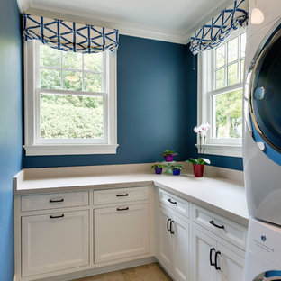 Mid-sized elegant l-shaped porcelain floor and beige floor dedicated laundry room photo in Minneapolis with white cabinets, concrete countertops, blue walls, a stacked washer/dryer, beige countertops and recessed-panel cabinets