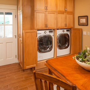 Large elegant single-wall porcelain floor and brown floor utility room photo in San Diego with shaker cabinets, medium tone wood cabinets, quartz countertops, beige walls and a side-by-side washer/dryer