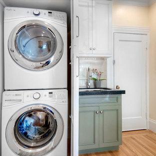 Foto på en liten vintage linjär tvättstuga, med luckor med infälld panel, vita skåp, granitbänkskiva, beige stänkskydd, stänkskydd i keramik, en undermonterad diskho, beige väggar, ljust trägolv och en tvättpelare
