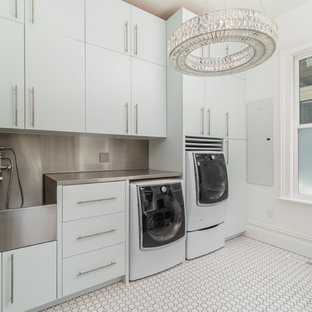 Example of an ornate porcelain floor and white floor laundry room design in San Francisco with flat-panel cabinets, white cabinets, stainless steel countertops, white walls and a side-by-side washer/dryer
