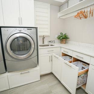 Foto di una sala lavanderia vittoriana di medie dimensioni con lavello sottopiano, ante con riquadro incassato, ante bianche, top in marmo, pareti grigie, pavimento con piastrelle in ceramica, lavatrice e asciugatrice affiancate e pavimento grigio