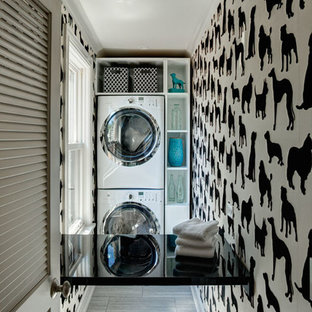 Example of a small eclectic ceramic floor dedicated laundry room design in Chicago with open cabinets, white cabinets, a stacked washer/dryer and multicolored walls
