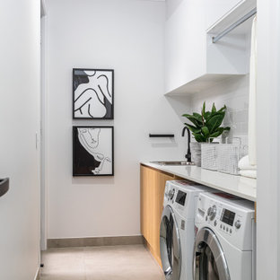 Photo of a mid-sized contemporary single-wall dedicated laundry room in Brisbane with a drop-in sink, flat-panel cabinets, medium wood cabinets, white walls, a side-by-side washer and dryer, grey floor and white benchtop.