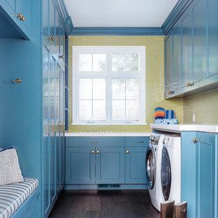 Immagine di una lavanderia multiuso tradizionale di medie dimensioni con ante in stile shaker, ante blu, parquet scuro e lavatrice e asciugatrice affiancate