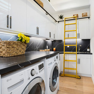 Bild på en mellanstor funkis svarta l-formad svart tvättstuga enbart för tvätt, med släta luckor, vita skåp, ljust trägolv och en tvättmaskin och torktumlare bredvid varandra