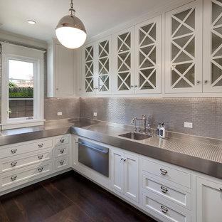 Idéer för en klassisk tvättstuga, med luckor med glaspanel, vita skåp, bänkskiva i rostfritt stål, mörkt trägolv och brunt golv