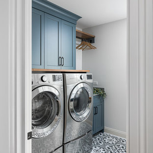 This is an example of a large traditional single-wall utility room in Chicago with white walls, porcelain flooring, shaker cabinets, blue cabinets, a side by side washer and dryer and multi-coloured floors.