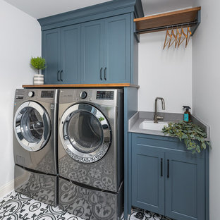 Photo of a large transitional laundry room in Chicago with flat-panel cabinets, white cabinets, white walls, porcelain floors and brown floor.