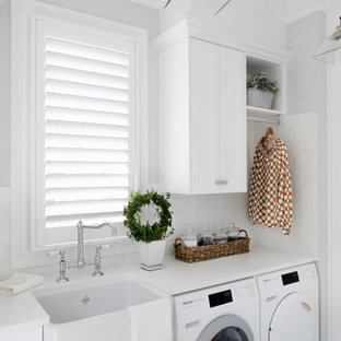 Mid-sized transitional single-wall dedicated laundry room in Brisbane with a farmhouse sink, shaker cabinets, white cabinets, white splashback, subway tile splashback, grey walls, a side-by-side washer and dryer, grey floor and white benchtop.