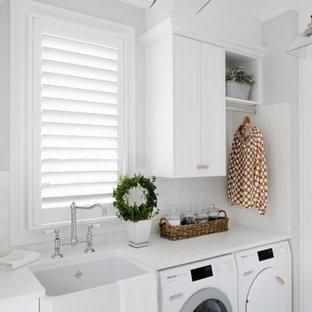 Ispirazione per una sala lavanderia tradizionale di medie dimensioni con lavello stile country, ante in stile shaker, ante bianche, paraspruzzi bianco, paraspruzzi con piastrelle diamantate, pareti grigie, lavatrice e asciugatrice affiancate, pavimento grigio e top bianco