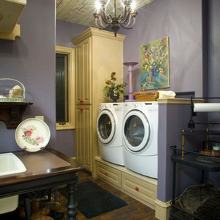 Example of a mid-sized country galley dark wood floor laundry room design in Orange County with raised-panel cabinets, purple walls, a side-by-side washer/dryer and white cabinets