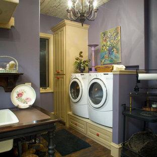 Bild på en mellanstor lantlig parallell tvättstuga, med luckor med upphöjd panel, lila väggar, en tvättmaskin och torktumlare bredvid varandra, vita skåp och mörkt trägolv