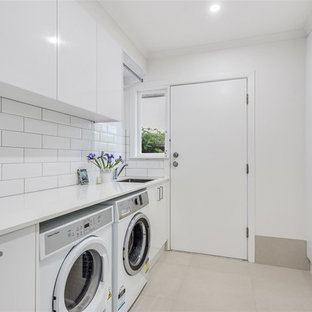 Design ideas for a mid-sized contemporary galley dedicated laundry room in Gold Coast - Tweed with an undermount sink, flat-panel cabinets, white cabinets, quartzite benchtops, white walls, a side-by-side washer and dryer, grey floor and white benchtop.