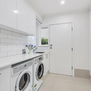 Idee per una sala lavanderia contemporanea di medie dimensioni con lavello sottopiano, ante lisce, ante bianche, top in quarzite, pareti bianche, lavatrice e asciugatrice affiancate, pavimento grigio e top bianco