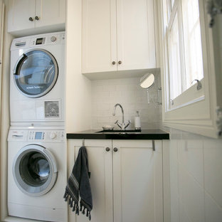 Inspiration for a small classic single-wall separated utility room in Sydney with shaker cabinets, white cabinets, white walls, limestone flooring and a stacked washer and dryer.