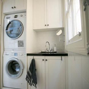 Immagine di una piccola sala lavanderia chic con ante in stile shaker, ante bianche, pareti bianche, pavimento in pietra calcarea e lavatrice e asciugatrice a colonna