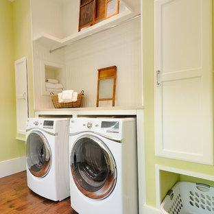 Inspiration för mellanstora klassiska linjära tvättstugor, med en tvättmaskin och torktumlare bredvid varandra, öppna hyllor, vita skåp, mellanmörkt trägolv och gröna väggar