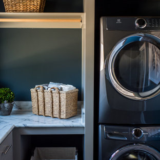 Immagine di una sala lavanderia classica di medie dimensioni con lavello da incasso, ante in stile shaker, ante grigie, pareti blu, pavimento in legno massello medio, lavatrice e asciugatrice a colonna, pavimento marrone e top grigio