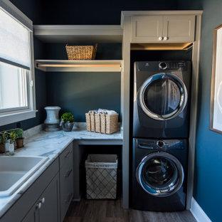 Esempio di una sala lavanderia tradizionale di medie dimensioni con lavello da incasso, ante in stile shaker, ante grigie, pareti blu, pavimento in legno massello medio, lavatrice e asciugatrice a colonna, pavimento marrone e top grigio