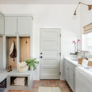 Foto på en mellanstor vintage vita l-formad tvättstuga enbart för tvätt, med en undermonterad diskho, skåp i shakerstil, gröna skåp, bänkskiva i kvarts, vitt stänkskydd, vita väggar, klinkergolv i terrakotta, en tvättmaskin och torktumlare bredvid varandra och rött golv