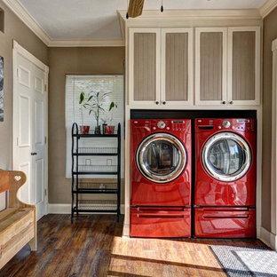 Bild på en stor vintage tvättstuga, med luckor med infälld panel, beige skåp, beige väggar, mörkt trägolv och en tvättmaskin och torktumlare bredvid varandra