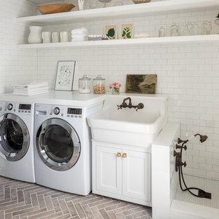 ボストンのカントリー風おしゃれな家事室 (エプロンフロントシンク、オープンシェルフ、白いキャビネット、白い壁、レンガの床、左右配置の洗濯機・乾燥機、白いキッチンカウンター) の写真