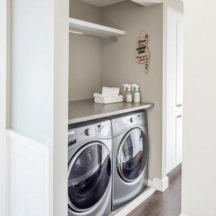 Foto på en mycket stor vintage grå linjär liten tvättstuga, med en rustik diskho, skåp i shakerstil, vita skåp, laminatbänkskiva, beige väggar, laminatgolv, en tvättmaskin och torktumlare bredvid varandra och brunt golv